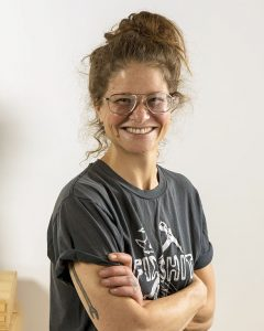woman with crossed arms and glasses smiles