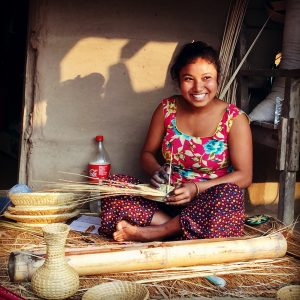 women sitting making a basket