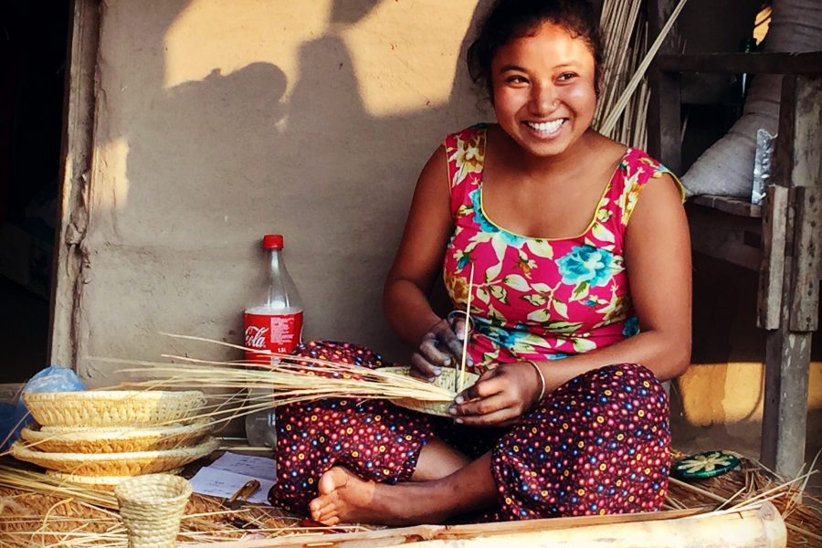 Someone smiling making woven pottery